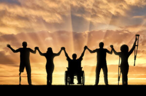Disabled and healthy holding hands sunset