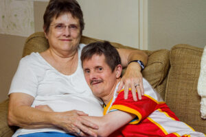 An older man with Downs Syndrome, hugs his mother as they sit on a couch. The woman looks tired, the man looks mischievous. He is about to tickle her.