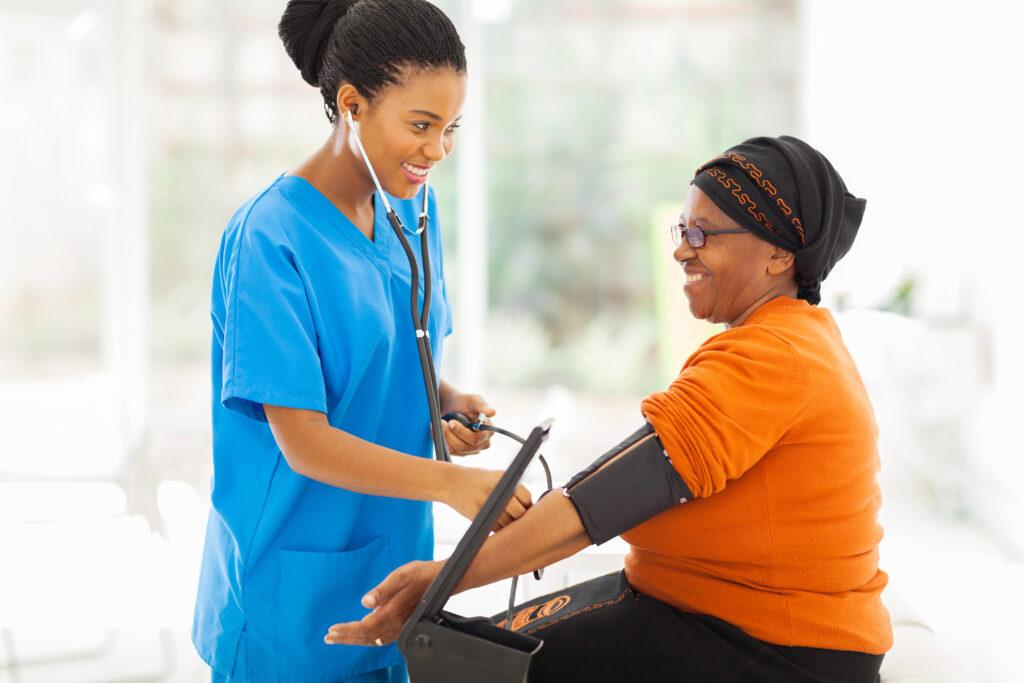 smiling african nurse checking senior patient's blood pressure